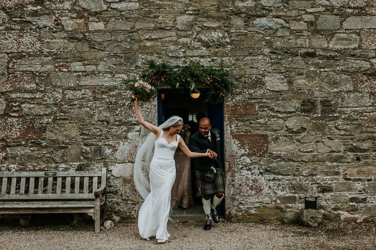 Bride and groom celebrate wedding with hanging flowers