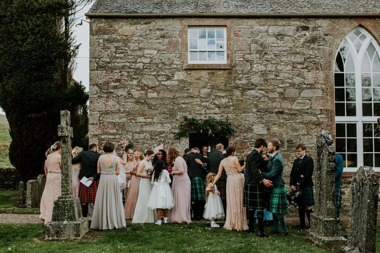 Wedding party gathers outside church for wedding with hanging flower decor
