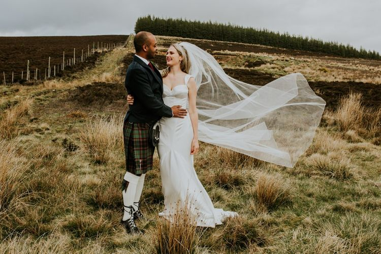 Brides veil blows in the wind for Scottish wedding with hanging flowers