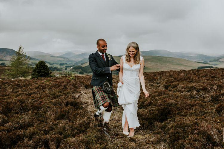 Bride and groom stroll through fields at Scottish wedding