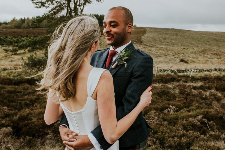 Bride and groom steal a moment during wedding with hanging flowers