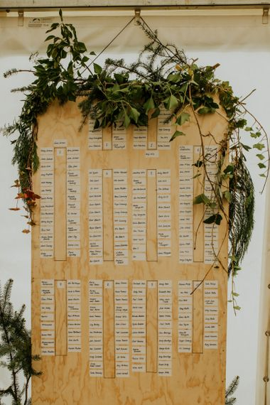 Wooden wedding table plan with foliage decor