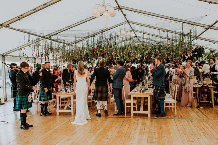 Bride and groom mingle with guests underneath hanging flowers