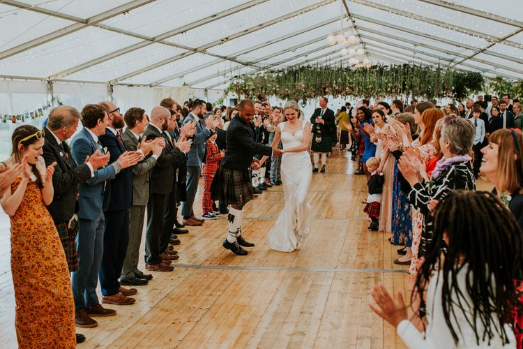 Scottish ceilidh underneath hanging flowers at marquee wedding