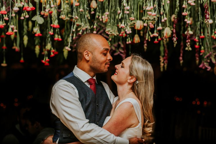 Bride and groom underneath hanging flowers