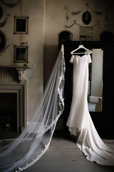 Raciela Pronovias Wedding Dress and Lace Edged Veil Hanging Up