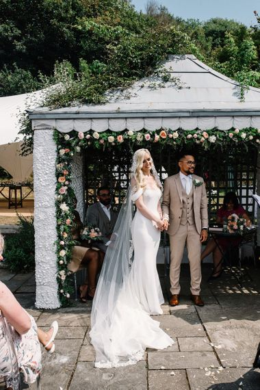 Bride and Groom Standing Under The Flower Covered Pergola at Their Outdoor Wedding Ceremony