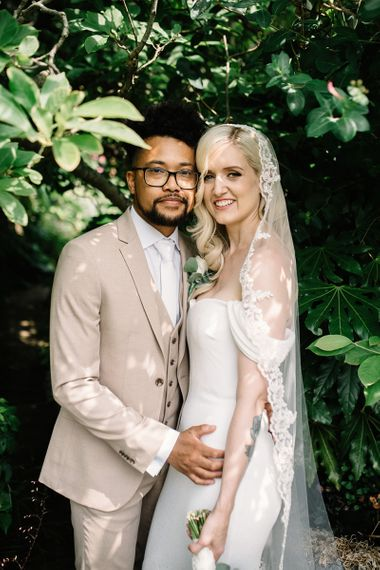 Beautiful Bride in Bardot Pronovias Wedding Dress and Groom in Beige Moss Bros. Suit