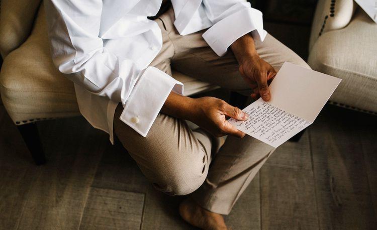 Groom in Beige Moss Bros. Suit Reading a Wedding Card