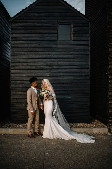 Bride in Pronovias Wedding Dress and Groom in Beige Moss Bros. Suit  Standing in Front of a  Shed Backdrop
