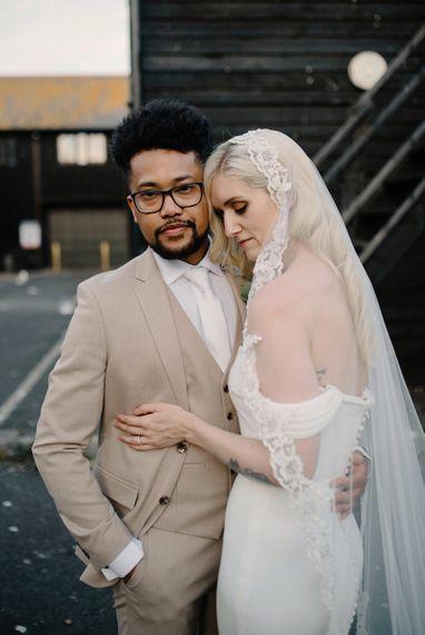 Bride in Pronovias Wedding Dress Embracing her Groom in a Beige Moss Bros. Suit
