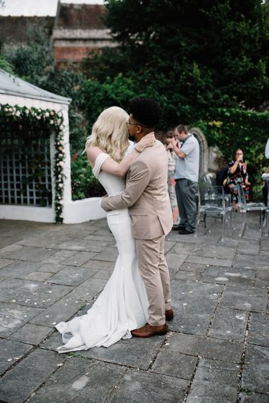 Bride in Pronovias Wedding Dress and Groom in a Beige Moss Bros. Suit Having Their First Dance Together