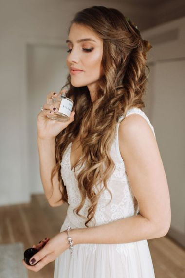Bride with Long Brunette Wavy Hair Putting On Perfume on the Wedding Morning