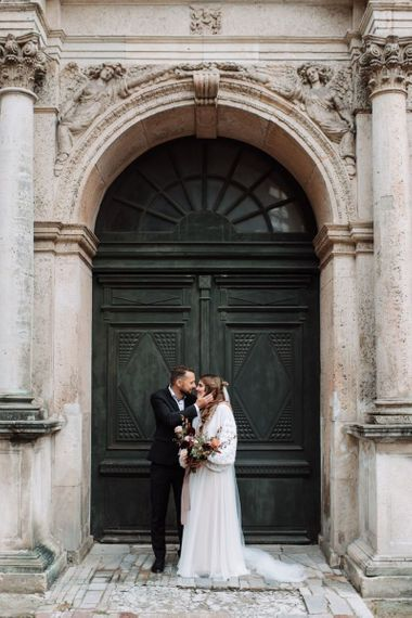 Groom in Black Suit Kissing His Bride in a Katya Katya Wedding Dress and Knitted Coverup