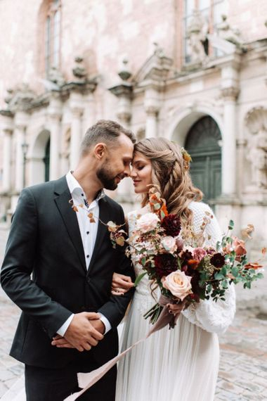 Groom in Black Suit and White Skirt and Bride in Knitted Coverup Holding a Deep Red and Pink Wedding Bouquet