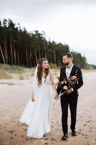 Bride in Fay Katya Katya Wedding Dress with Long Wavy Hair and Groom in Black Suit Holding Hands Walking Along The Beach