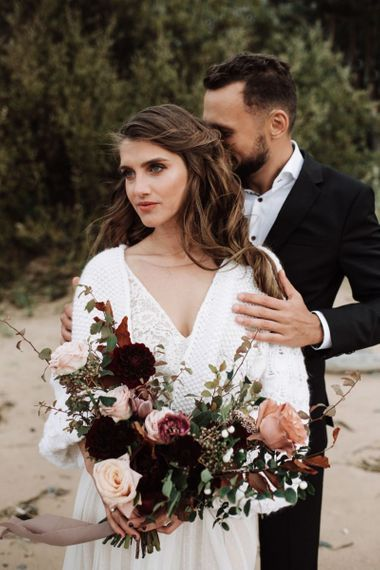 Beautiful Bride in Katya Katya Wedding Dress with Wool Coverup Holding a Deep Red and Pink Rose Wedding Bouquet
