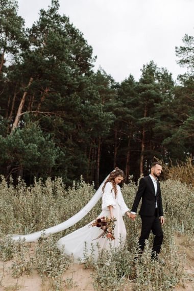 Groom in Black Suit Holding His Brides Hand in a Katya Katya Wedding Dress with Wool Coverup and Cathedral Length Veil