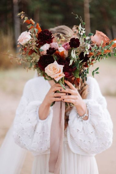 Bride in Wool Coverup Holding a Muted Pink and Red Wedding Bouquet Tied with Ribbon