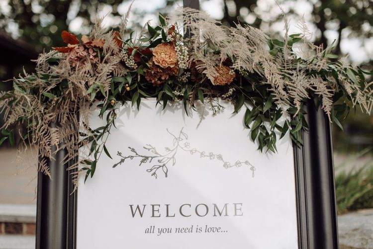 Wedding Welcome Sign Decorated with Muted Wedding Flowers and Dried Foliage