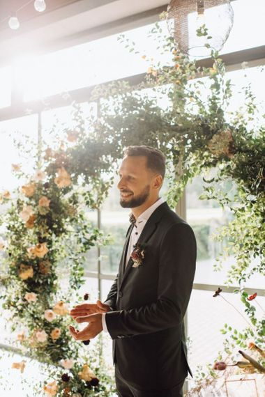 Groom in Black Suit Clapping at the Floral Moon Gate Altar