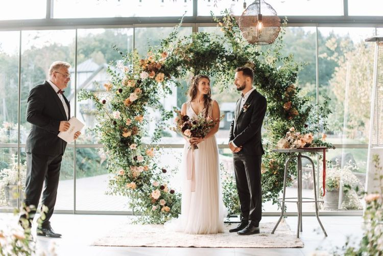 Celebrant Leading the Wedding Ceremony with the Bride and Groom Standing in Front of the Foliage and Flower Filled Moon Gate