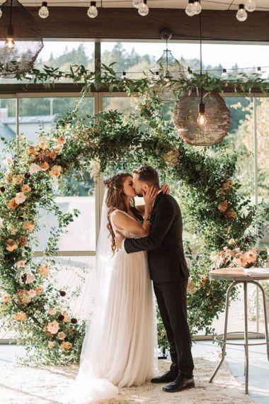 Bride in Katya Katya Wedding Dress and Groom in Black Suit Kissing at the Floral Moon Gate Altar
