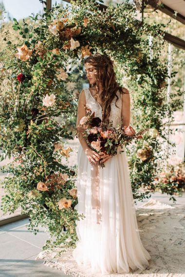 Bride in Fay Katya Katya Wedding Dress Standing in Front of a Floral Moon Gate holding a Bridal Bouquet