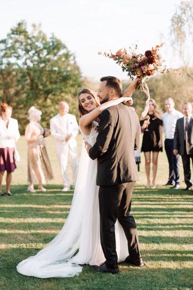 Outdoor First Dance with Bride in Katya Katya Wedding Dress and Groom in Black Suit