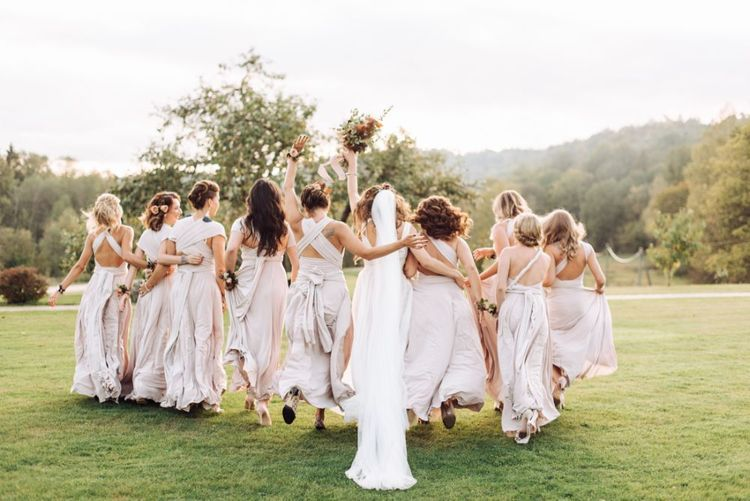 Bridal Party Portrait with Bridesmaids in Oyster Multiway Dresses and Bride in Fay Katya Katya Wedding Dress Skipping Through The Fields