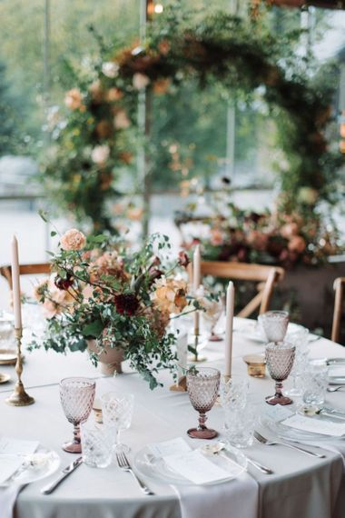 Wedding Reception Table Decor with Floral Centrepiece, Taper candles and Coloured Goblets