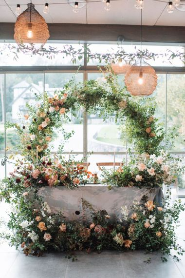 Sweetheart Table with Moon Gate Backdrop and Floral Arrangements in Front of The Table