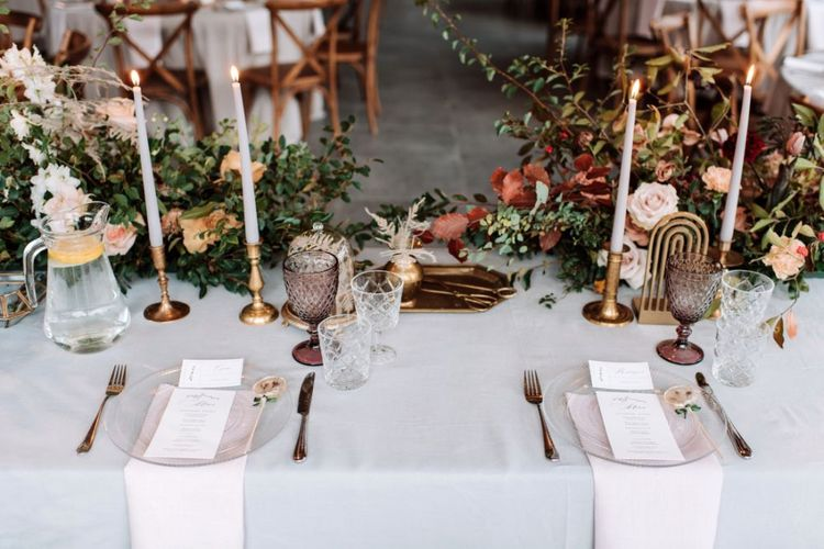 Sweetheart Table Place Settings with Gold Candlesticks, Glass Charger Plates and muted Flower Arrangements