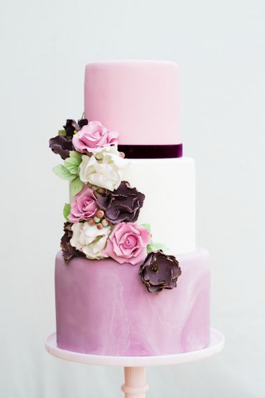 Delicieux Three Tiered Pink Iced Cake with Flowers