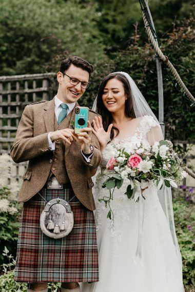 Bride and groom face timing family and friends