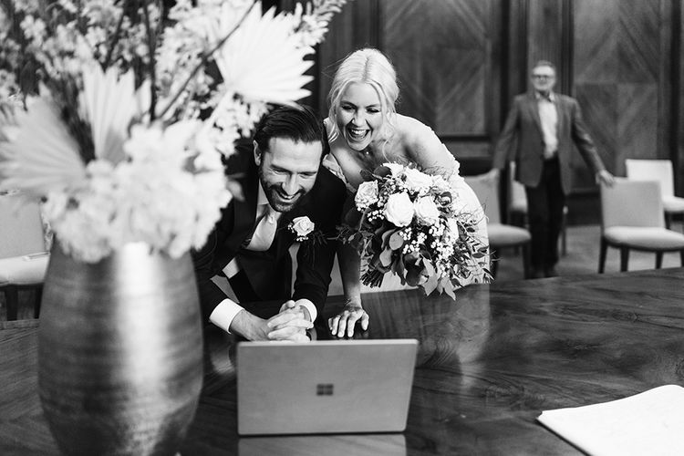 Bride and groom streaming a Zoom call during their wedding ceremony