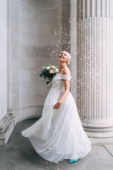 Bride in maternity wedding dress dancing under a confetti cannon at wedding for 15 people