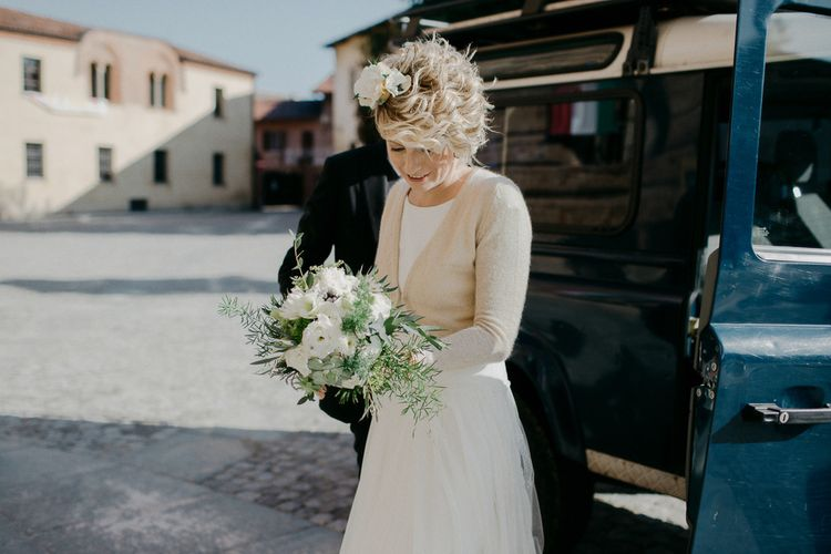 Bride in cardigan and flowers in her short hair