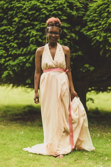 Bride in blush wedding dress and gold hair accessory