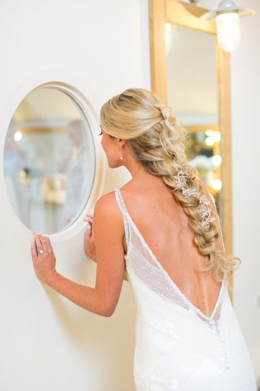 Bride looking in the mirror with long loose plait with trailing flowers