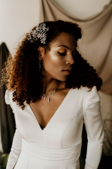 Black bride in bridal jumpsuit with curly hair