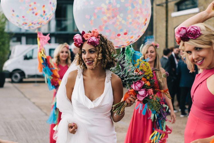 Bride with curly hair and pink flower crown holding a giant balloon