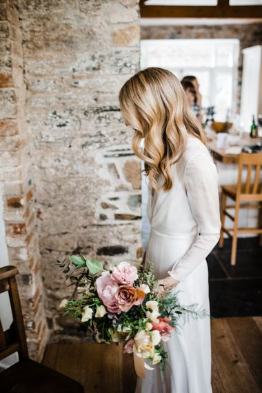 Bride in Andrea Hawkes Wedding Dress with Long Sleeves and Wavy Hair