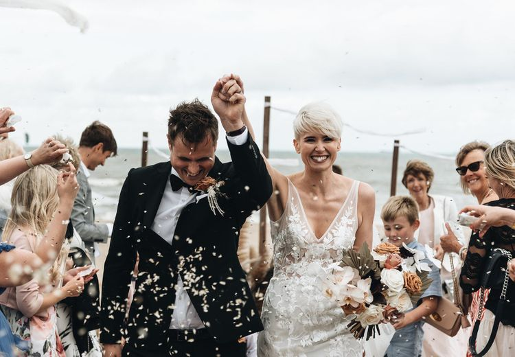 Confetti moment with bride with short hair in Made With Love wedding dress and groom in tuxedo