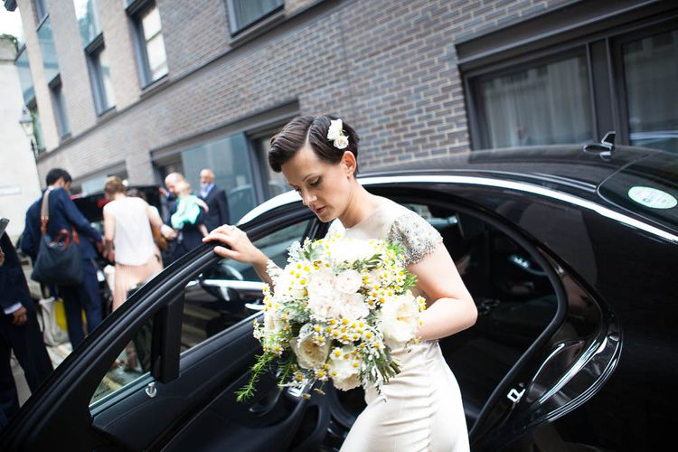 Bride with short hair getting out of wedding car