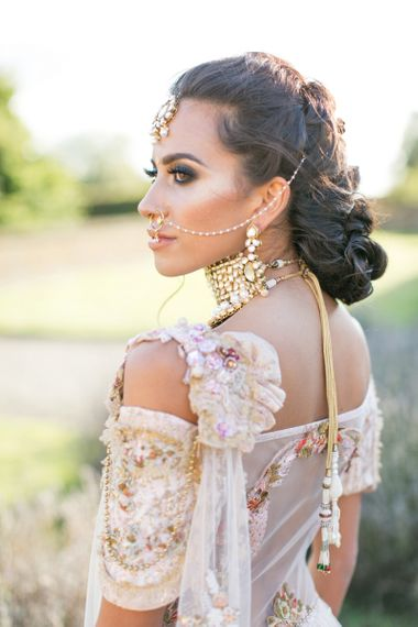 Asian bride with pinned hair and Indian accessories
