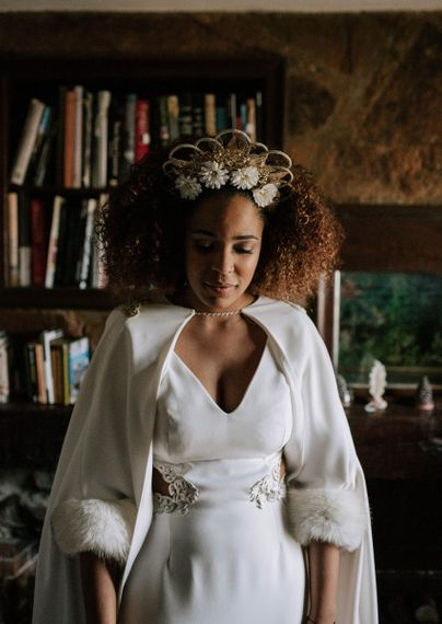 Beautiful black bride with curly hair in gold headdress and wedding cape