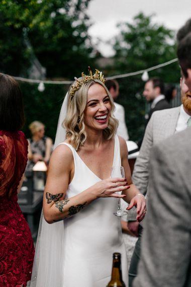 Stylish bride in  minimalist wedding dress and gold bridal crown