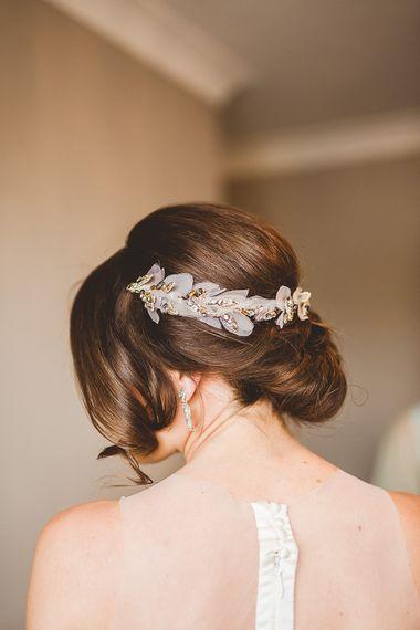 Low bun wedding hair with bridal accessory