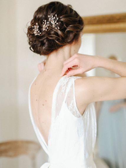 Pinned bridal updo with wedding hair accessories
